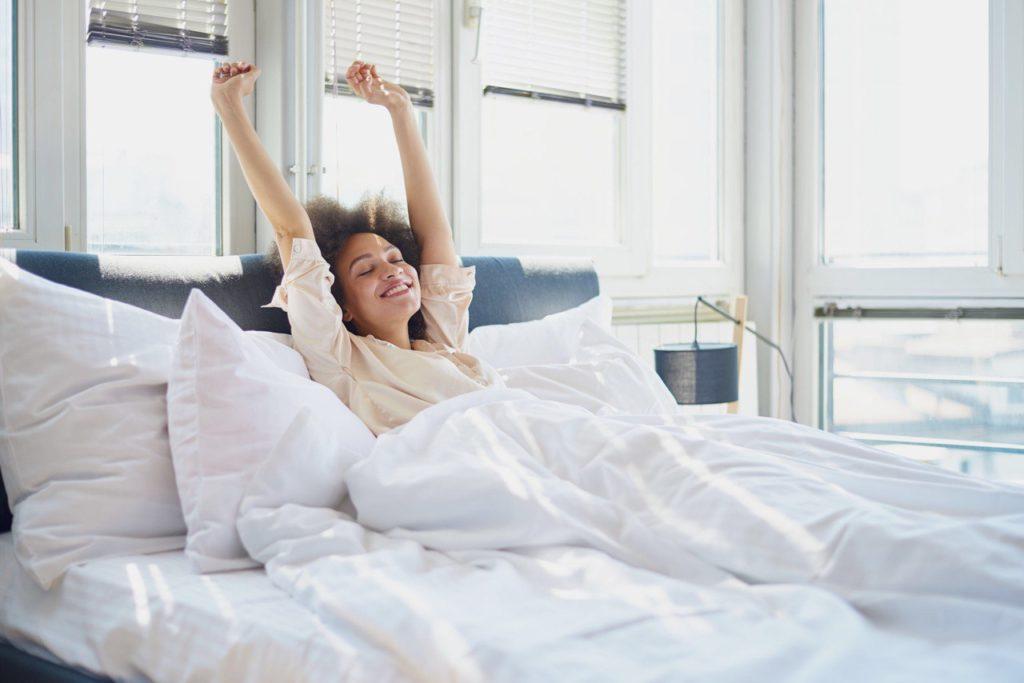 donna che si stiracchia al risveglio ancora stesa a letto