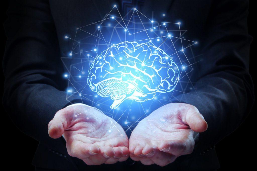 Ologramma di un cervello sospeso sopra le mani aperte di un uomo