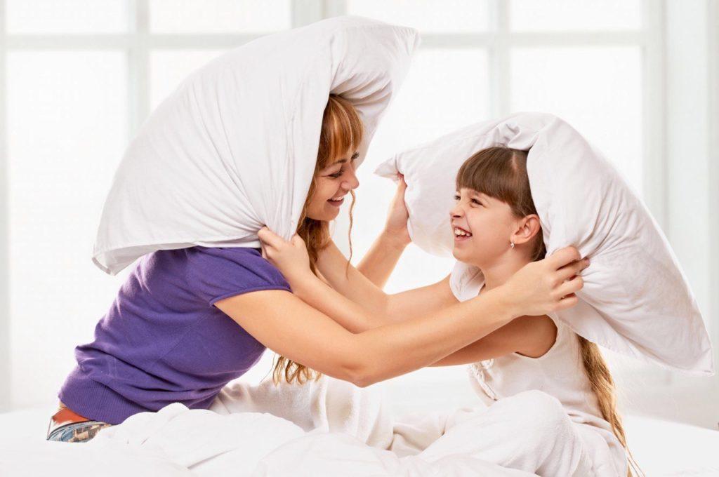 mamma e figlia  a letto che giocano con dei cuscini
