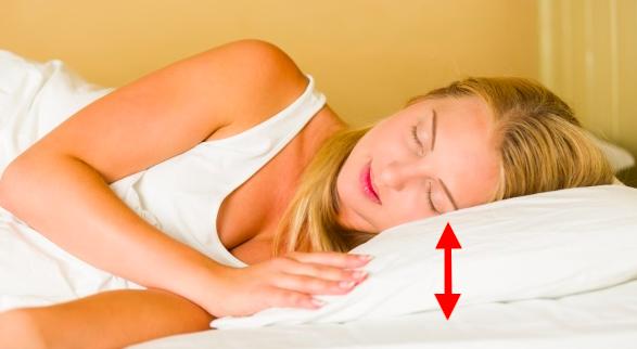 donna che dorme sul fianco con freccia che indica lo spazio tra l'orecchio e la spalla.