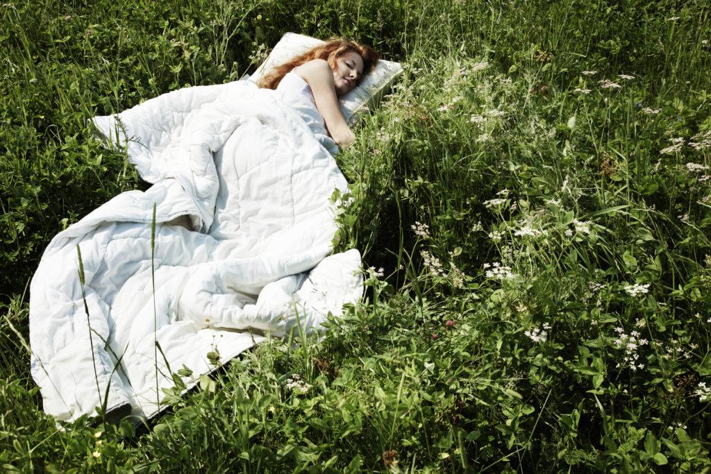 una donna stesa sull'erba coperta con un piumino da letto con la testa appoggiata ad un cuscino