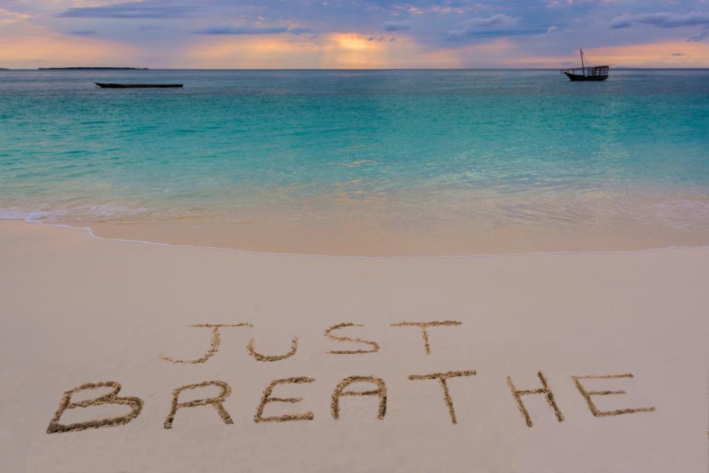 """mare azzurro con la spiaggia e tramonto all'orizzonte, con la scritta sulla spiaggia """"just Breathe"""""""
